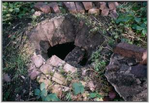 Hole in the semi-buried brick dome over shaft